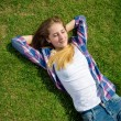 Teenager girl lying on back on grass at sunny day  — Stock Photo #54851313