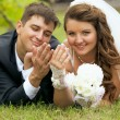 Newly married couple lying on grass and looking at wedding rings — Stock Photo #54852951