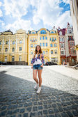 Young woman standing on paving road at old city — Stock Photo