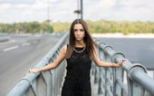 Dark haired woman in black dress posing on urban bridge — Stock Photo