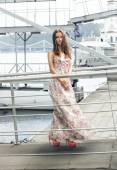 Slim woman in long dress posing on pier against bridge at windy  — Stock Photo