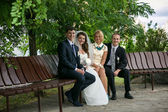 Married couple and two witnesses sitting on bench at park — Photo