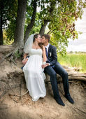 Bride and groom sitting under tree at river bank and kissing — Fotografia Stock