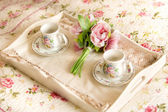 Vintage tray with flowers and teacups lying on bed — ストック写真