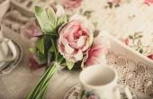 Retro styled photo of pink flowers lying on tray with teacups — Stock Photo