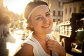Smiling woman with greek styled haircut on street at sun light — Stock Photo