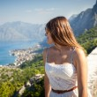 Beautiful brunette woman looking on sea from high mountain — Stock Photo #55208063