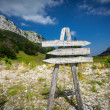 Signpost with three directions on the foot of big mountain — Stock Photo #55209031
