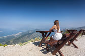 Woman siting on bench on top of mountain and looking at landscap — Stock Photo
