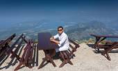 Smiling man sitting on bench at top of high mountain at sunny da — Stock Photo