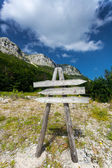 Wooden signpost on path to high mountain — Stock Photo