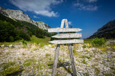 Signpost with three directions on the foot of big mountain — Stock Photo