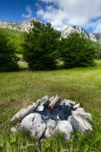 High mountain and extinguished campfire in forest — Stock Photo
