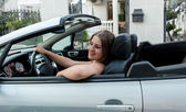 Smiling woman sitting in convertible and holding steering wheel — Stock Photo