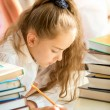 Brunette schoolgirl surrounded by books doing homework — Stock Photo #55878437