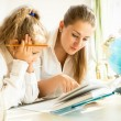 Mother and daughter reading textbook while doing homework — Stock Photo #55879153