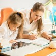 Girl using digital tablet while mother doing homework instead of — Stock Photo #55879321