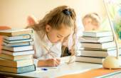 Concentrated schoolgirl surrounded by books doing homework — Stock Photo
