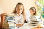 Smiling girl sitting at school desk and doing homework — Stock Photo