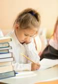 Ritratto di ragazza triste esercizio di scrittura nel libro di testo di una scuola — Foto Stock