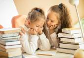 Older sister soothing younger one while doing homework — Stock Photo