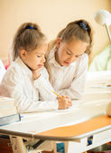 Two cute schoolgirls writing at textbook at desk — Stock Photo
