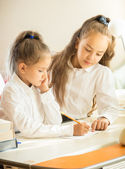 Portrait of older sister helping with homework to younger one — Stock Photo