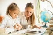 La mère assis avec la fille au comptoir et d'expliquer les tâches à la maison — Photo