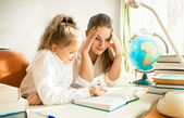 Confused mother looking at daughters complicated homework — Stock Photo
