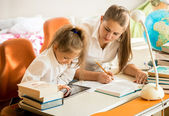 Girl with mother looking on tablet how to do homework — Stock Photo