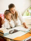 Mother pointing in exercise book and explaining homework to daug — Stock Photo
