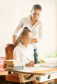Schoolgirl doing homework while mother watching at her — Stock Photo