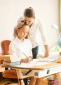 Mother hugging and praising daughter while doing homework — Stock Photo