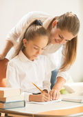Mother helping daughter with preparing to exam — Stock Photo