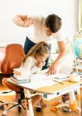 Man giving a cuff on nape to daughter doing homework — Stock fotografie