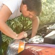 Man looking at open car hood and fixing engine — Stock Photo #55880037