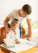 Young father looking at daughter doing homework — Stock Photo