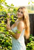 Smiling woman in garden holding apple and looking at camera — Stockfoto