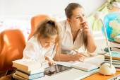 Mother sitting next to daughter doing homework — Foto de Stock