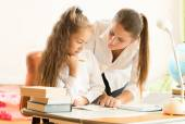 Beautiful mother helping daughter doing homework — Stock Photo