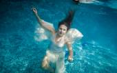 Woman with long hair swimming underwater at pool — Stock Photo