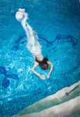 Woman in long white dress diving underwater at swimming pool — Stock Photo
