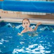 Young girl learning how to swim in pool — Stock Photo #55950891