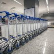 Ow of luggage trolleys at airport terminal — Stock Photo #55950979