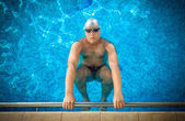 Male athlete holding on edge of swimming pool and preparing to s — Stock Photo