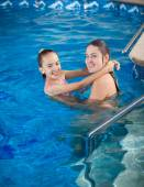 Mother holding daughter on water surface and teaching how to swi — Stock Photo
