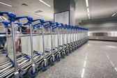 Ow of luggage trolleys at airport terminal — Stock Photo