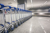 Baggage trolleys at arrival terminal in airport — Stock Photo