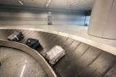 Luggage claim carousel with three bags at airport — Stock Photo