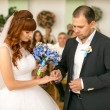 Handsome groom putting wedding ring on brides hand at registry o — Stock Photo #57590201